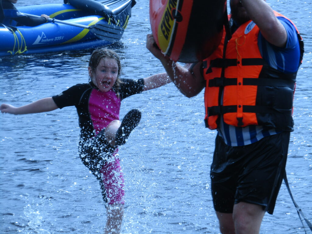 child and adult playing in water